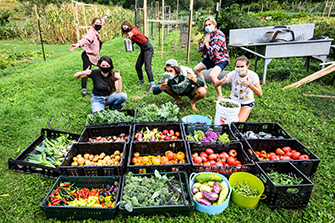 Students in front of a variety of vegetables