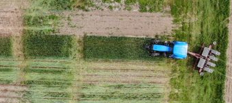 A tractor about to enter a crop field