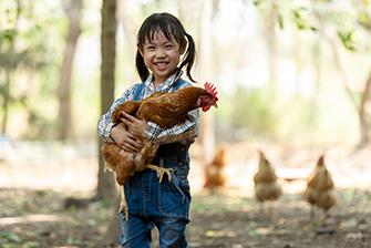 Little girl hold chicken in hand